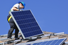 Worker on roof installing solar panelling